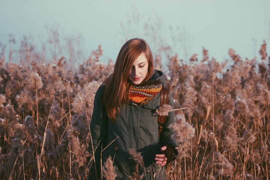 A redheaded woman wearing a winter coat and red scarf standing in a field