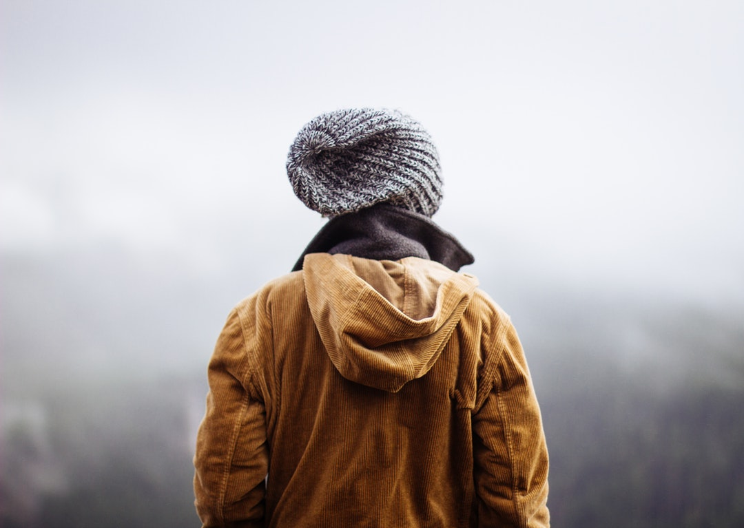 Person in winter jacket looks out a foggy forestscape on a hike