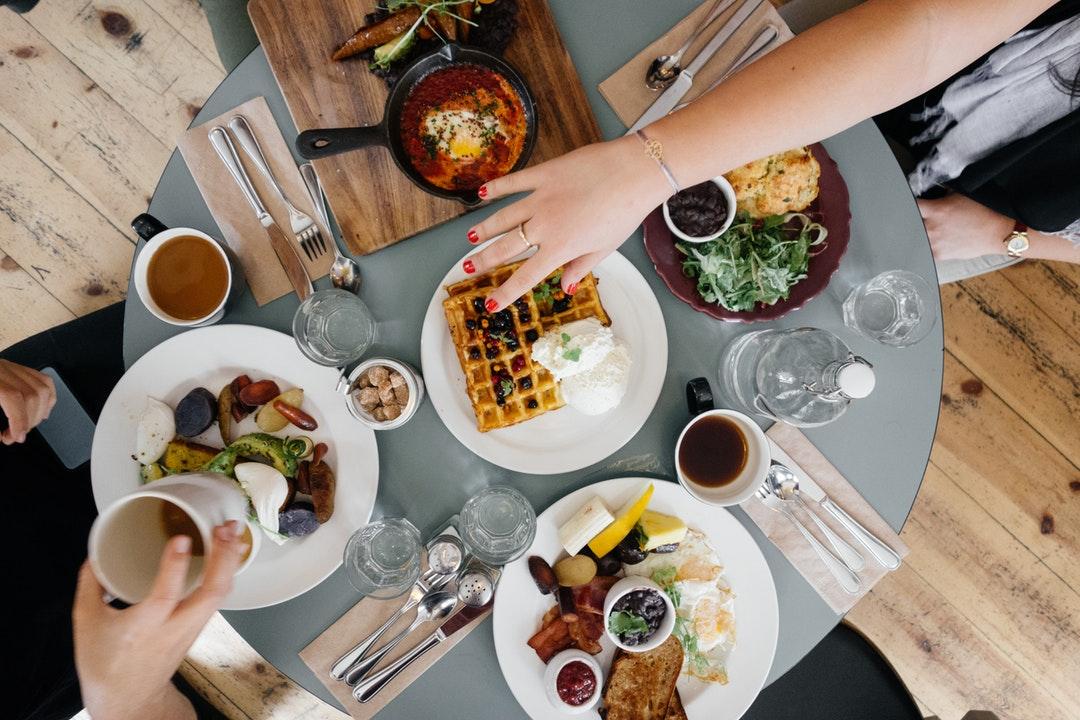 People eating huevos rancheros, waffles, and breakfast food for brunch