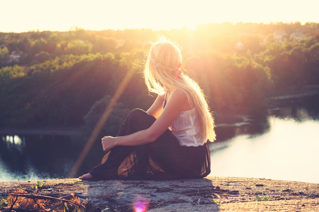 A young blonde woman sitting on rocks overlooking a lake
