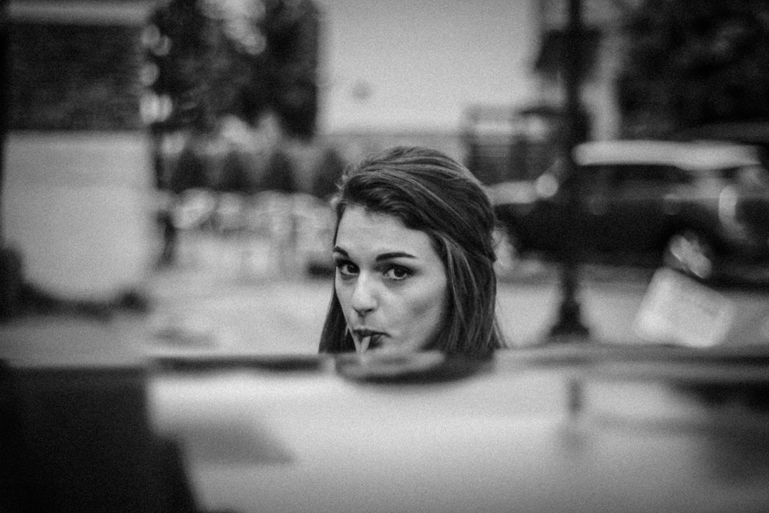 Black and white shot of attractive young woman sucking lollipop in street