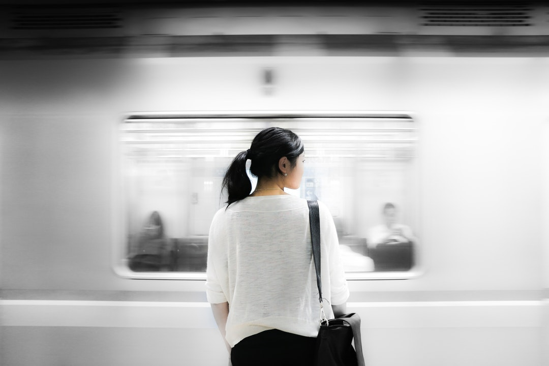 A subway train passing in front of a woman with a black leather bag