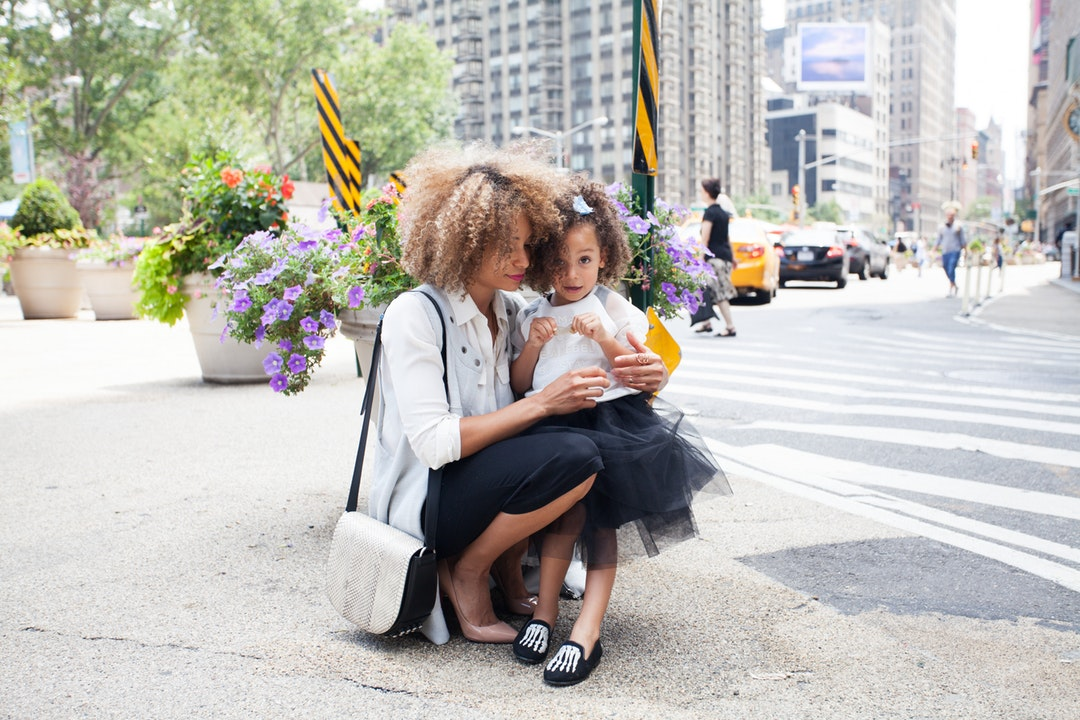 A mom and child, both with curly hair, cuddling in the street in New York