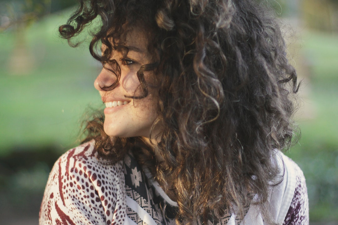 A smiling young woman with dark curly hair