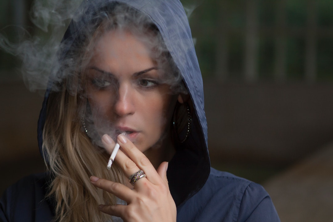 A blonde woman in a blue hoodie smoking a cigarette in Люберцы