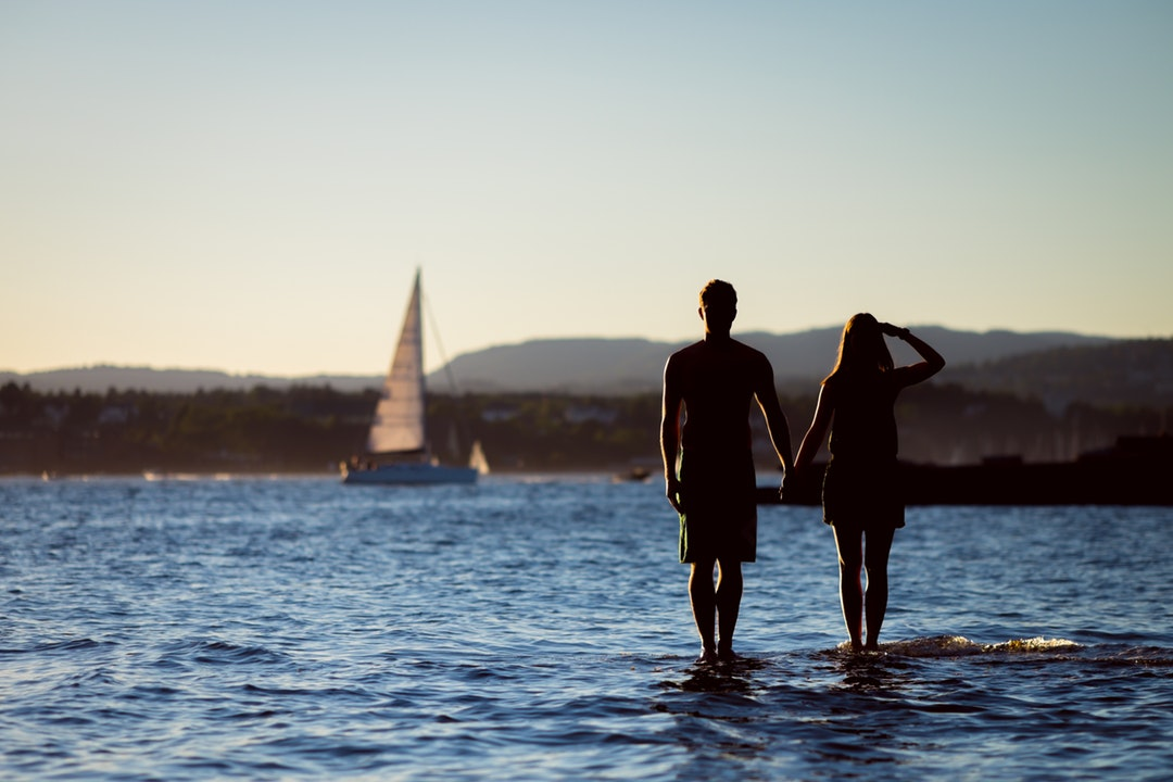 Man and woman standing in the bay watching a sailboat pass by