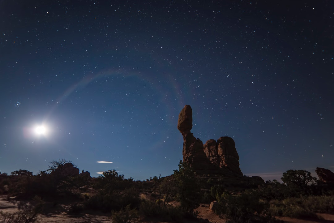 Bright moon over the rock formations on a starry night at Arches National Park