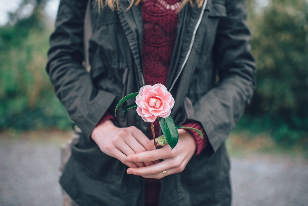 A woman in a jacket holding a small pink peony