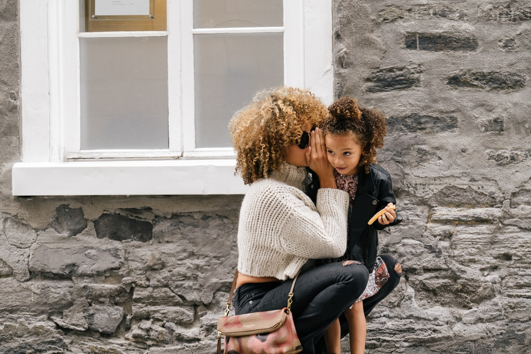 Mother with frizzy hair crouches down to tell daughter a secret on old city street