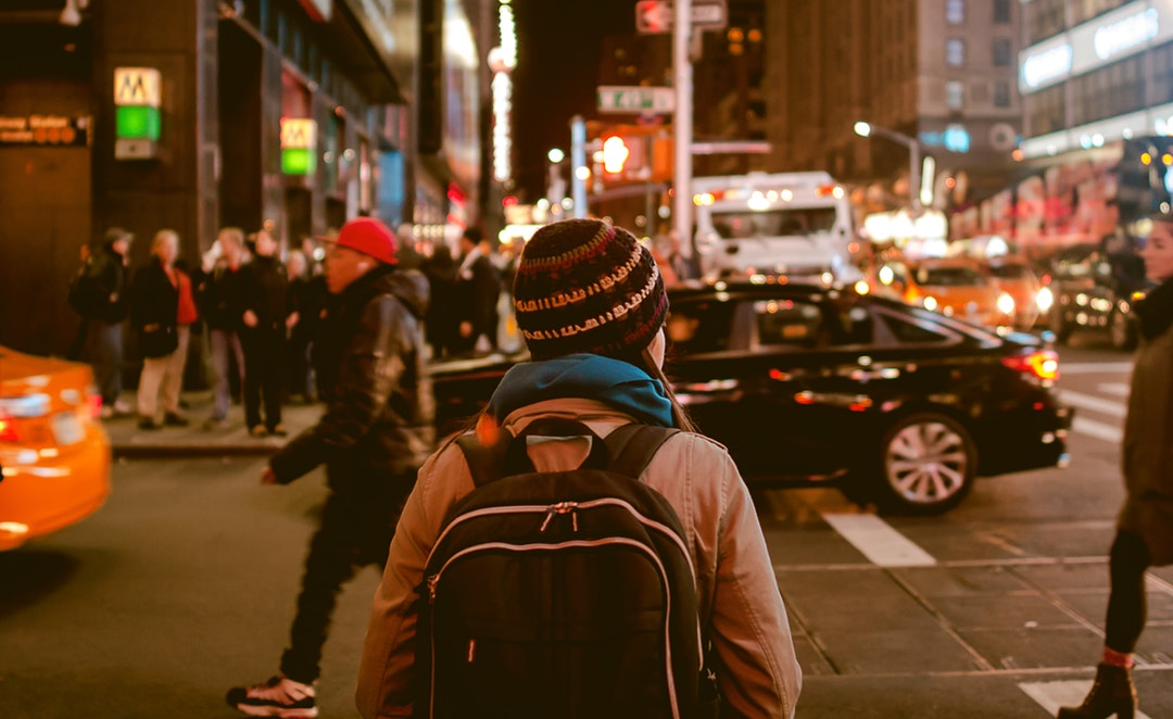 A backpacker in a knit cap in the streets of New York at night