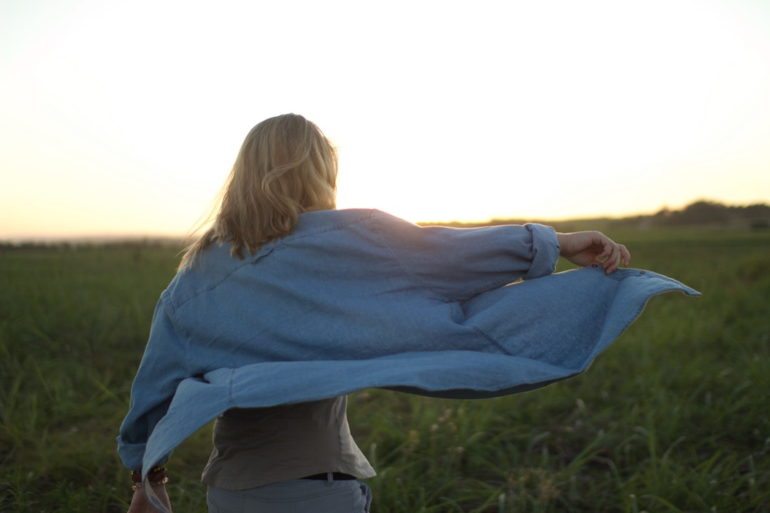 Woman in a blue shirt against a sunset in a field at Salt Rock.