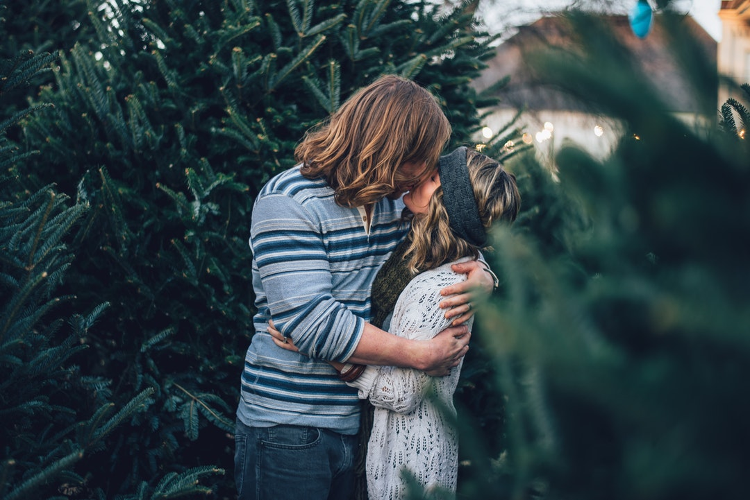 Couple kissing among pine trees in Nashville