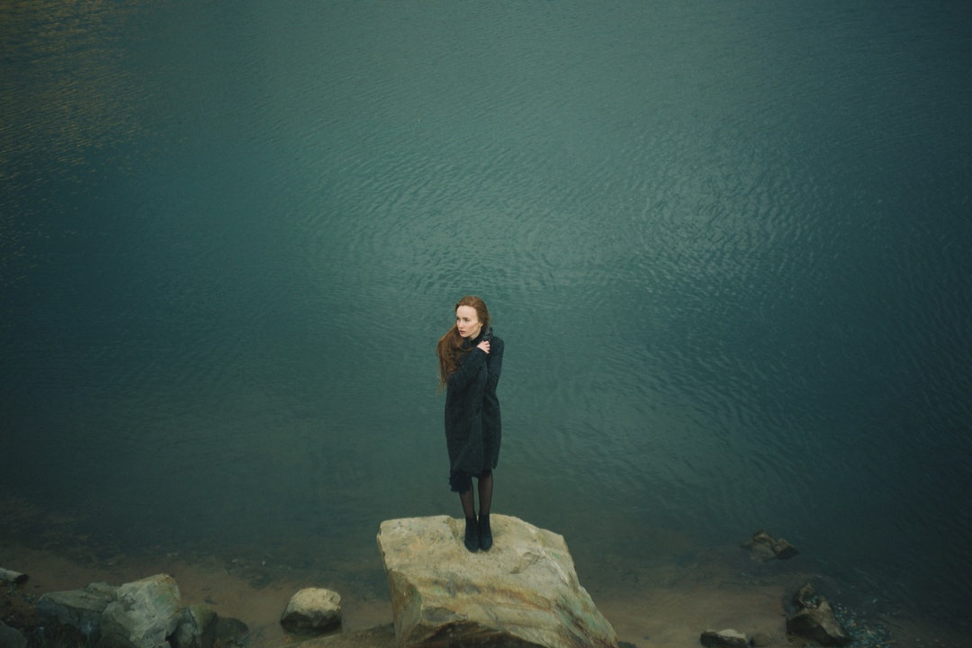 A redheaded woman bundled in a black sweater and black boots, standing on a rock next to a lake