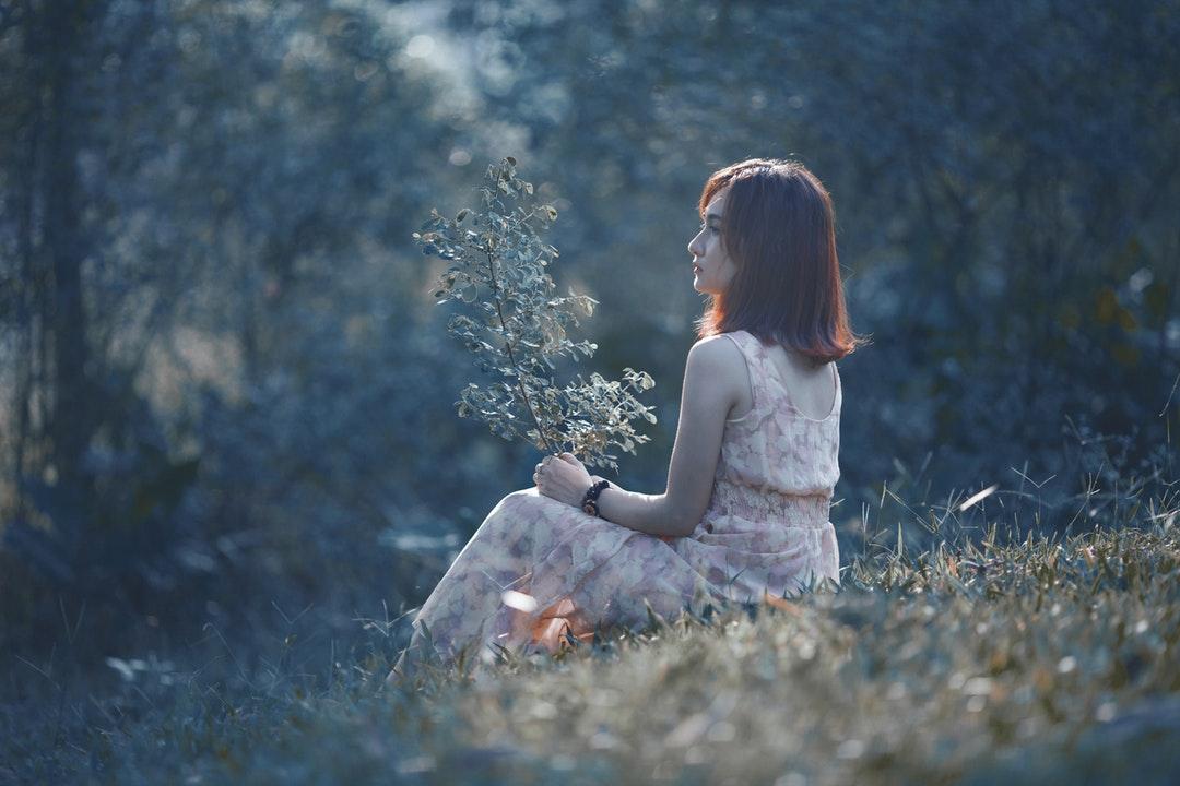 A woman sits on a grassy hill holding a tree branch in tp. Pleiku