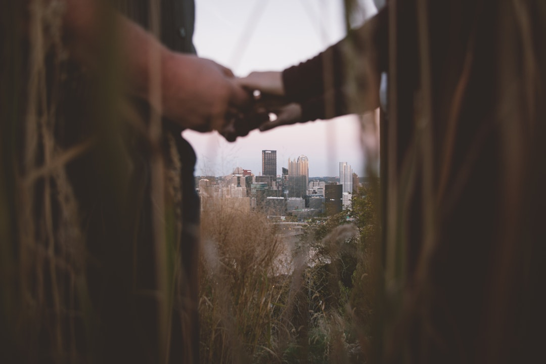 A couple is seen holding hands through tall grasses, with the Pittsburgh skyline in the background