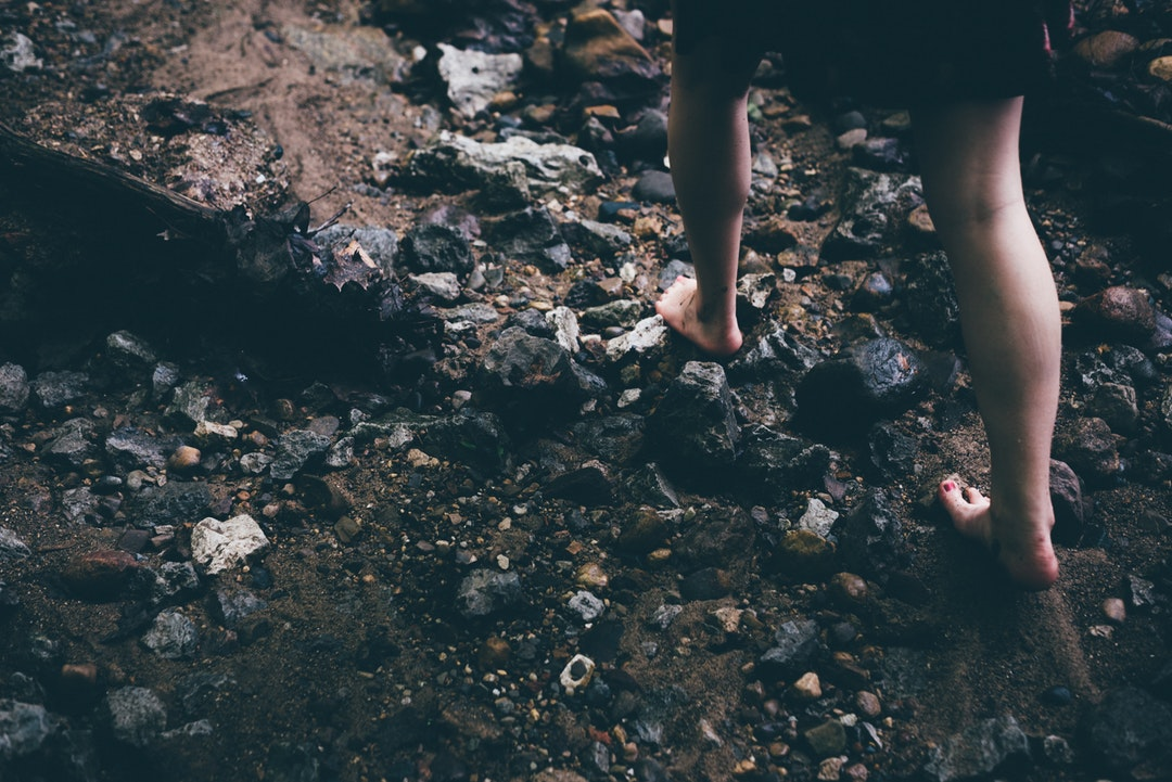 A barefoot girl walking over stones