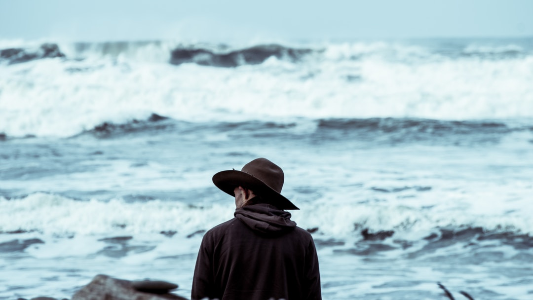 Man with a hat by the rough ocean at Ruby Beach