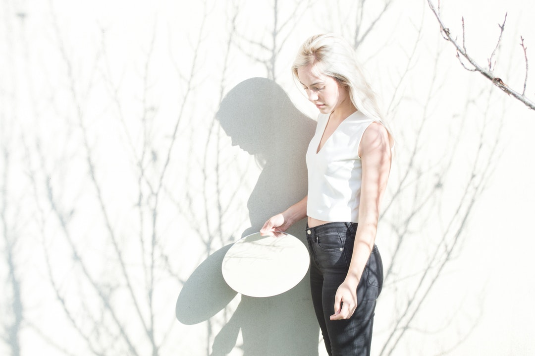 Woman in overexposed light holidng a circle mirror