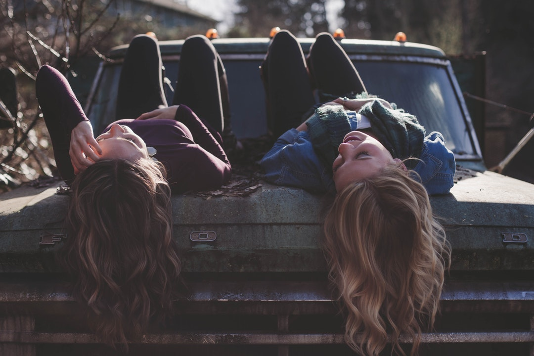 Teens girls lying on the hood of the old truck.