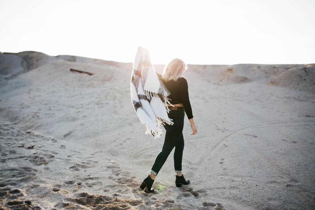 Fashionable woman walks with Aztec blanket throw white beach sand