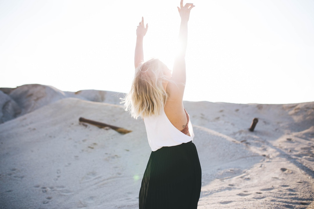 A blonde bowman lifting up her hands while standing on a sandy hill on a bright day