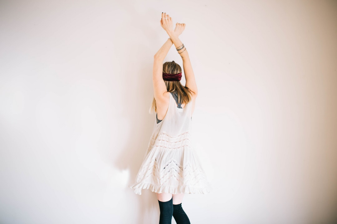 A woman in a white dress and black knee socks dancing near a wall