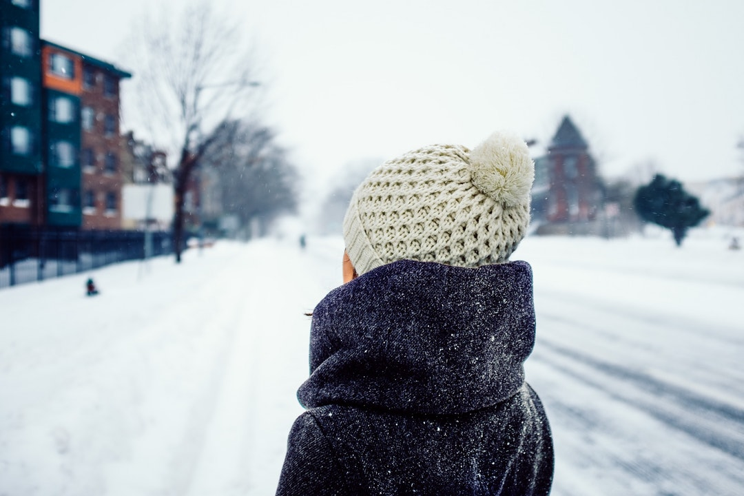 Person wearing a winter hat and coat standing in a snowy street