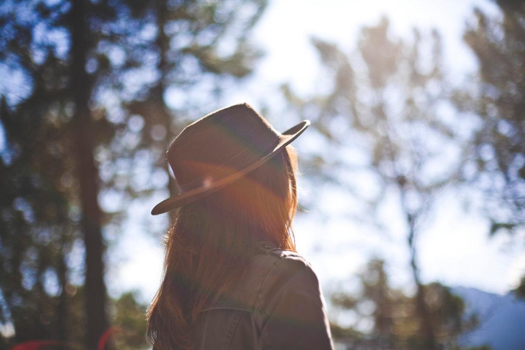 A hazy shot of a woman in a hat on a sunny day