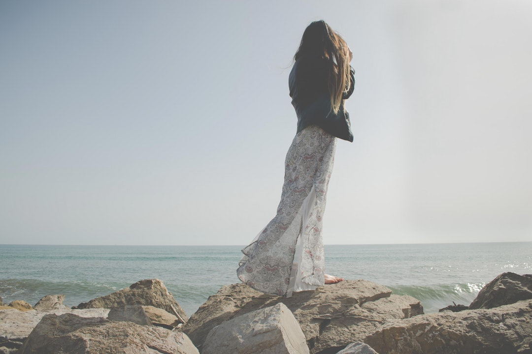 Woman in a dress standing on a rock at the Valencia coastline