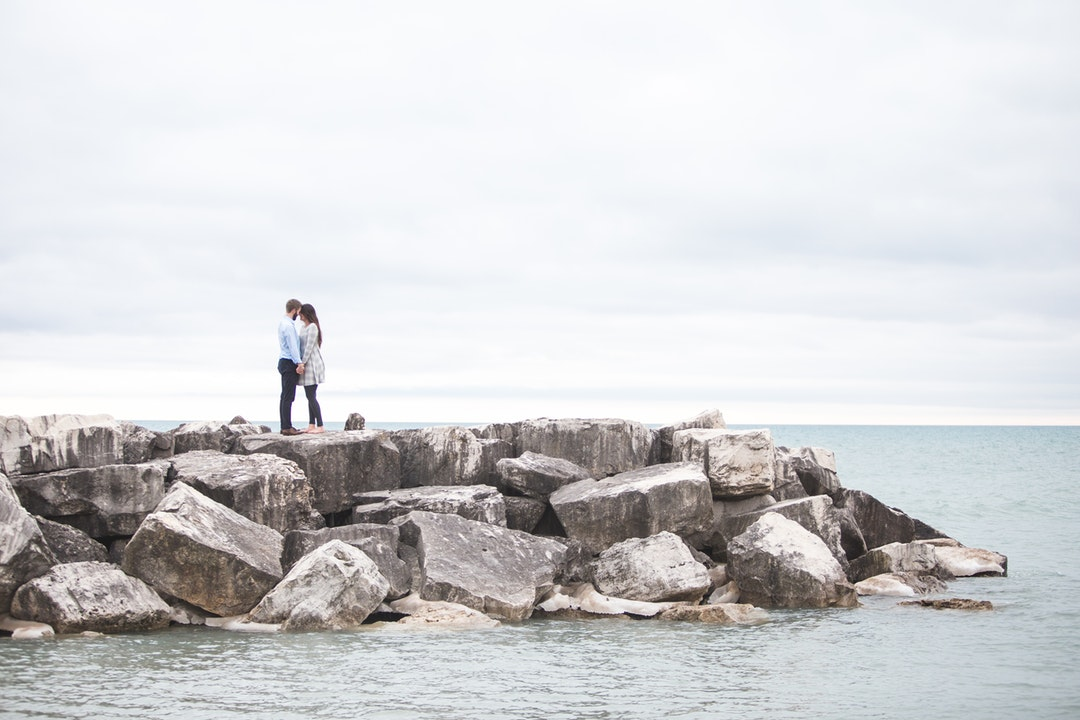 Standing on a stone jetty on the ocean, a couple shares a tender moment