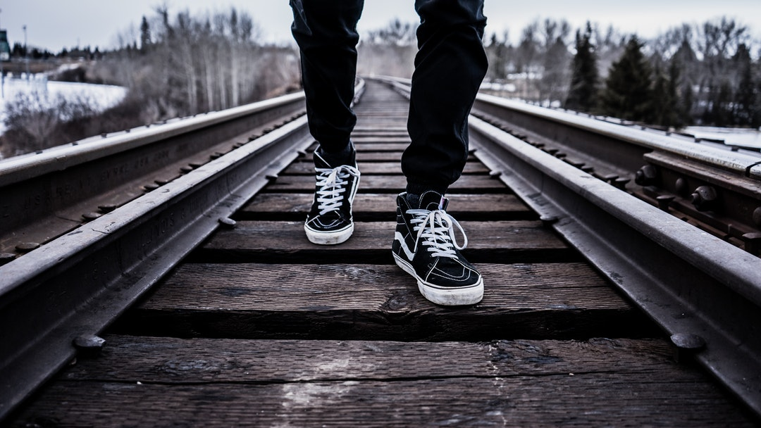 A person's feet in sneakers on a railroad track
