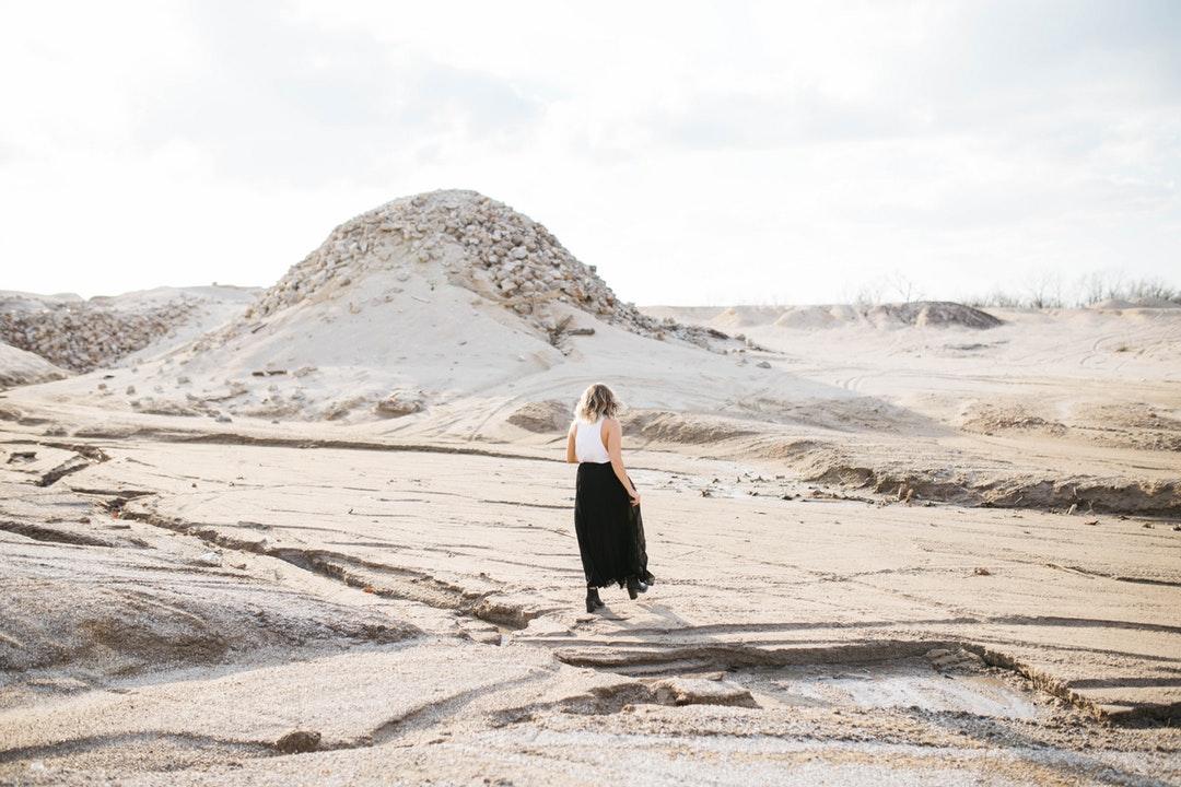 Fashionable woman walks alone through dry desert terrain