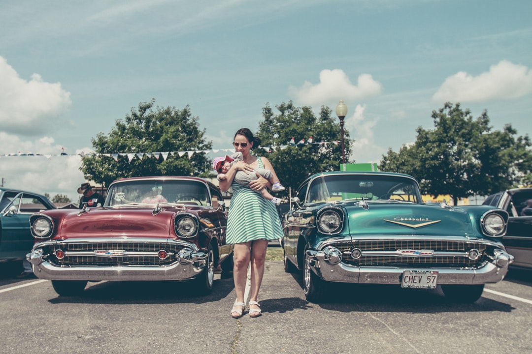 Woman carrying a baby standing in between two vintage cars