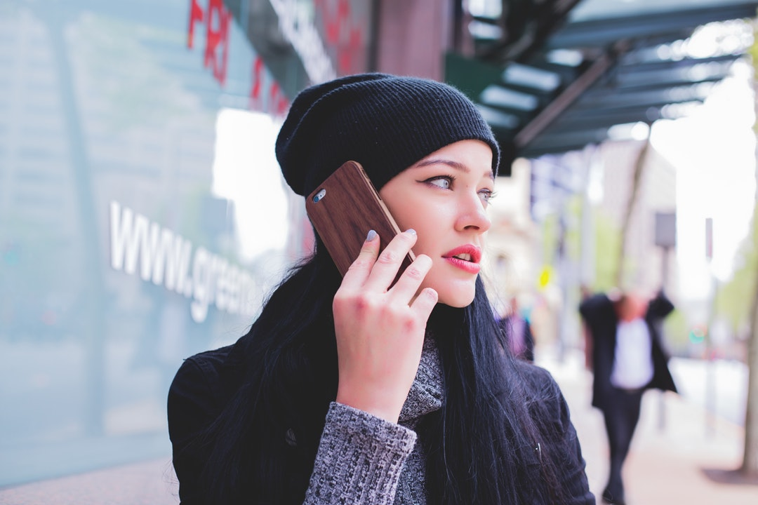A young woman in a beanie talking on a phone while standing on a sidewalk
