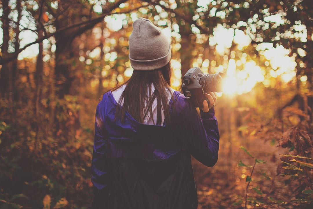 A woman in a beanie walking through a forest with a camera in her hand during sunset