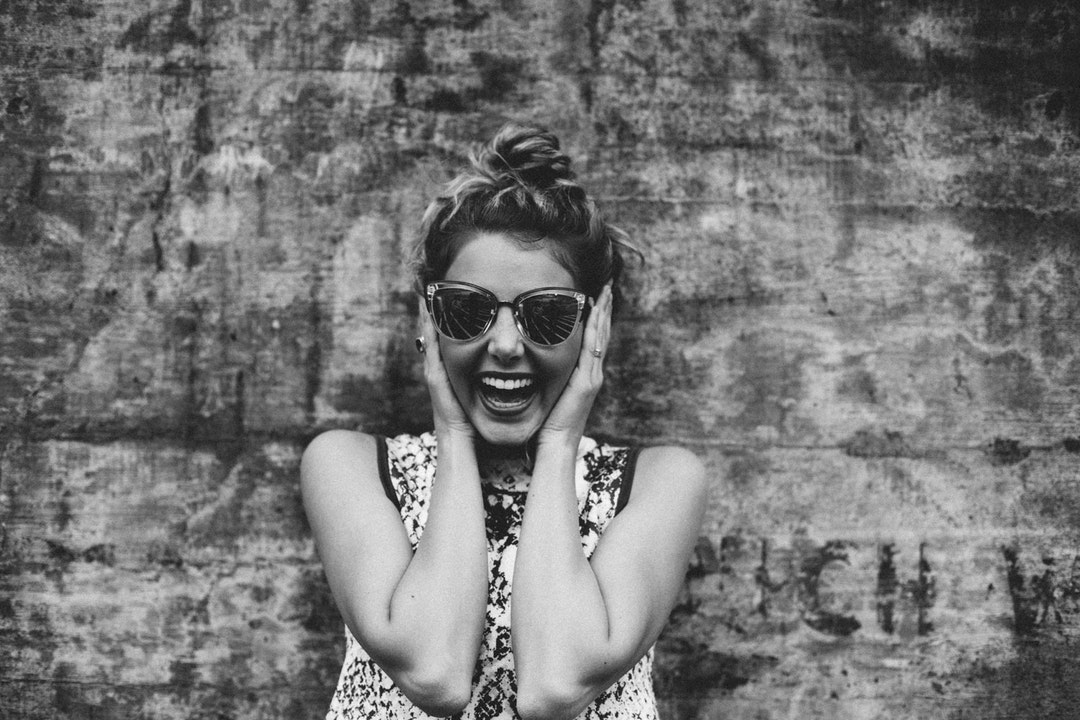 A woman with a large smile wearing sunglasses with her hands up on either side of her head