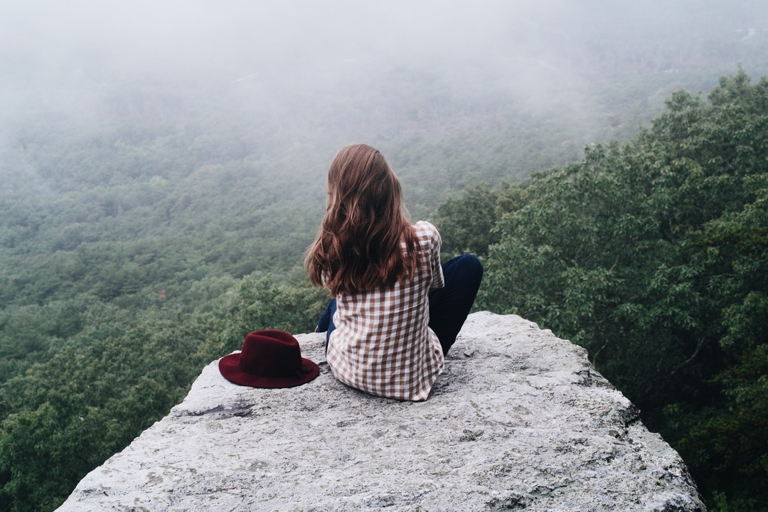 A lone woman sitting on a rocky ledge overlooking a forest with a red hat on her side