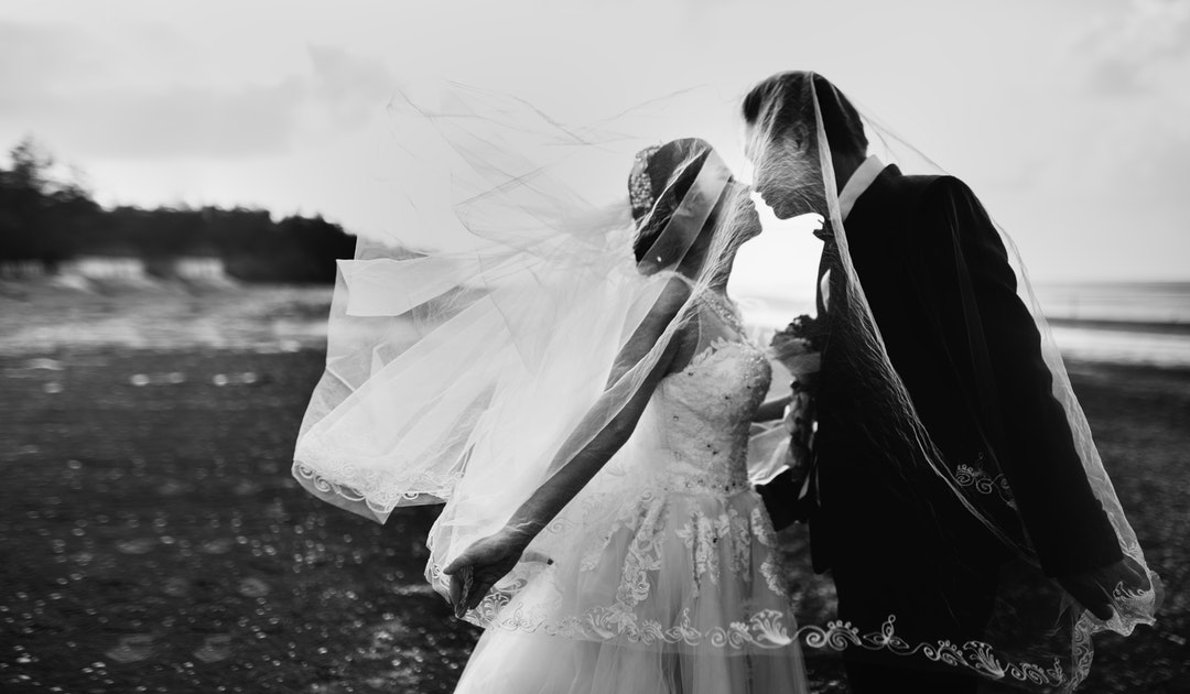 Black and white photo of a bride's veil flying up over her new husband as they kiss