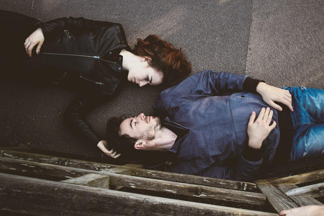 Overhead shot of man and woman laying on backs on walkway outdoors
