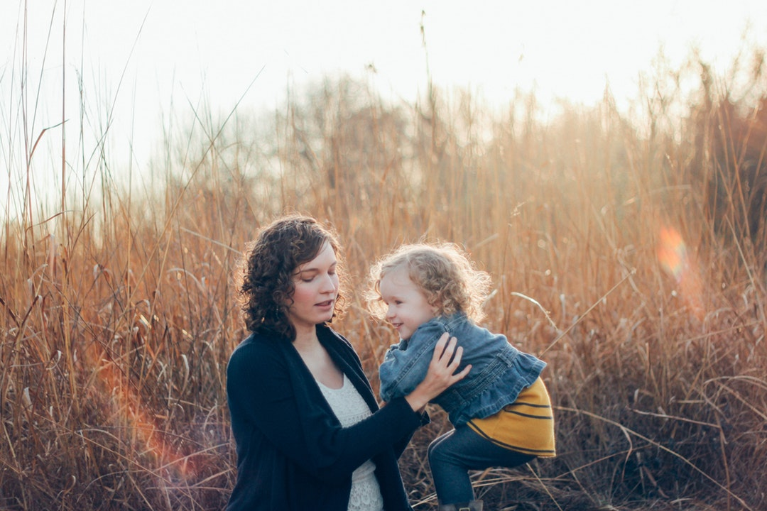Woman about to carry a happy toddler in a meadow in Illinois with the sun shining