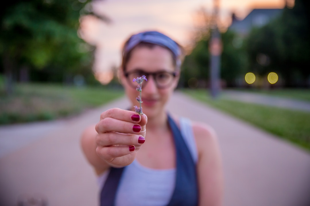 A woman in glasses holds out a flower on a path at the University of Illinois