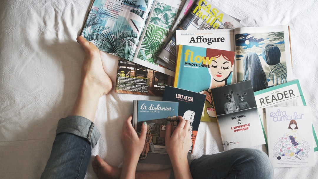 A woman sitting on her bed in jeans looking at several books and magazines in Milan