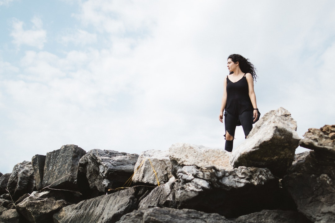 A woman wearing all black standing tall and proud on some rocks
