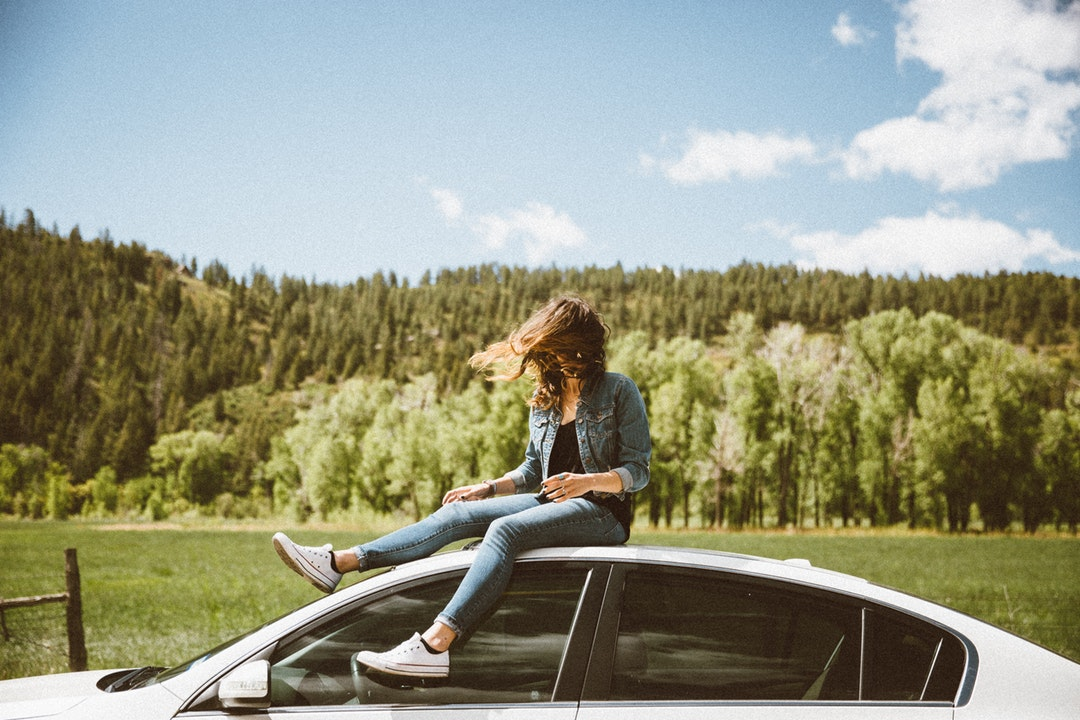 Young woman in denim sitting on white car roof with evergreen forest in background