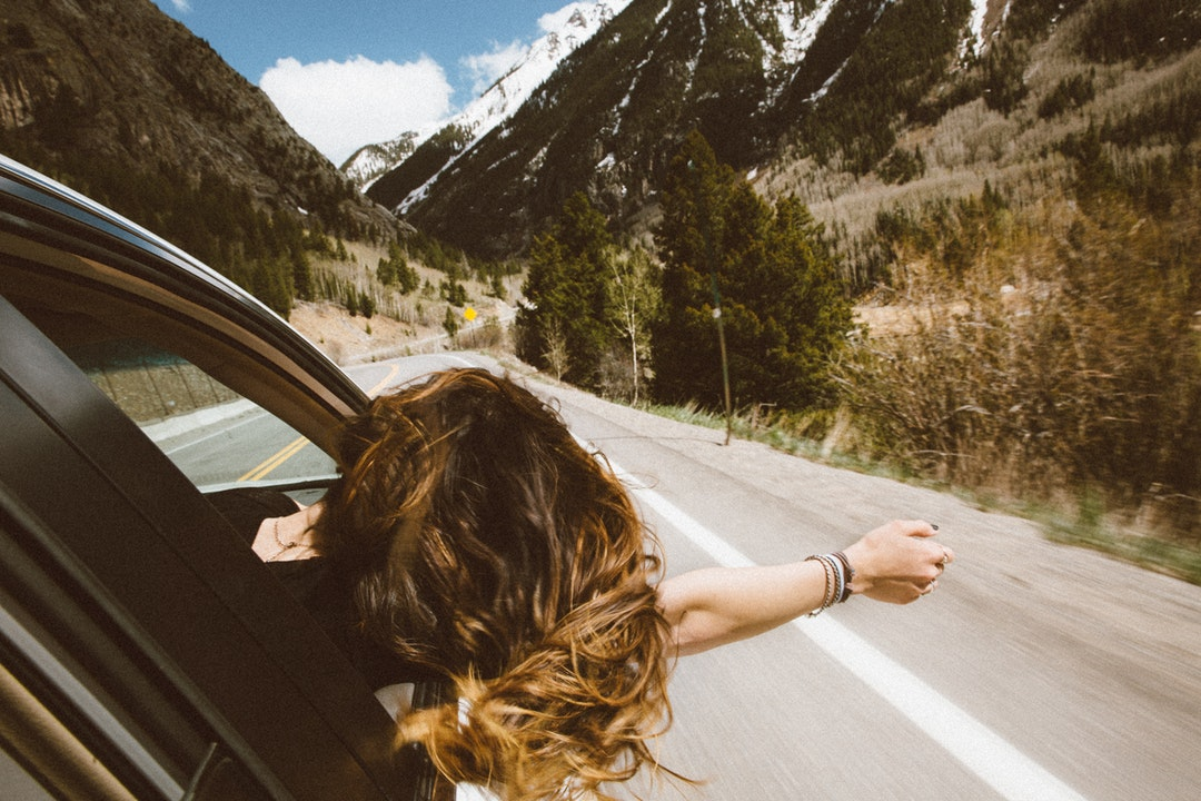 Young woman leans out car window to feel the fresh mountain air