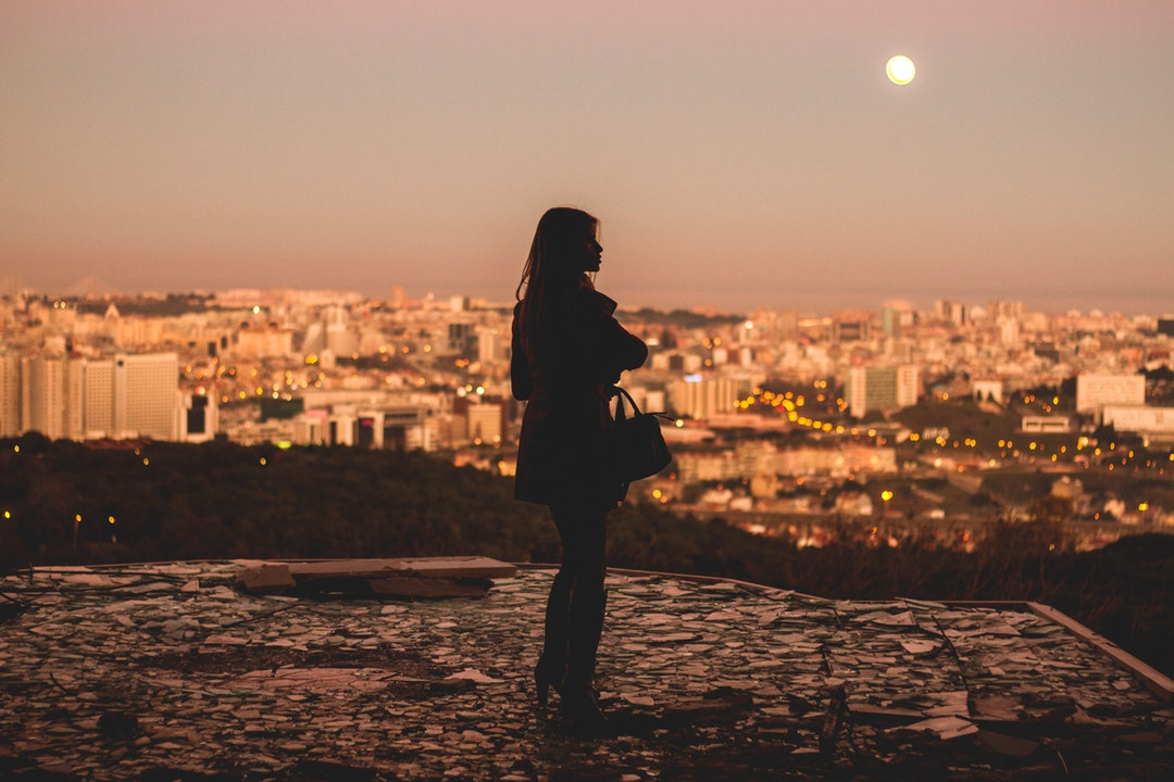 The silhouette of a woman looking across the cityscape of Lisbon during sunset.