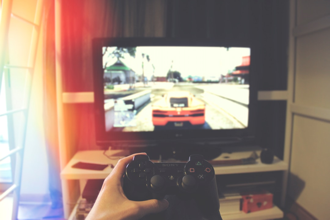 Person holding PS3 game controller and playing Grand Theft Auto on television under bunk bed