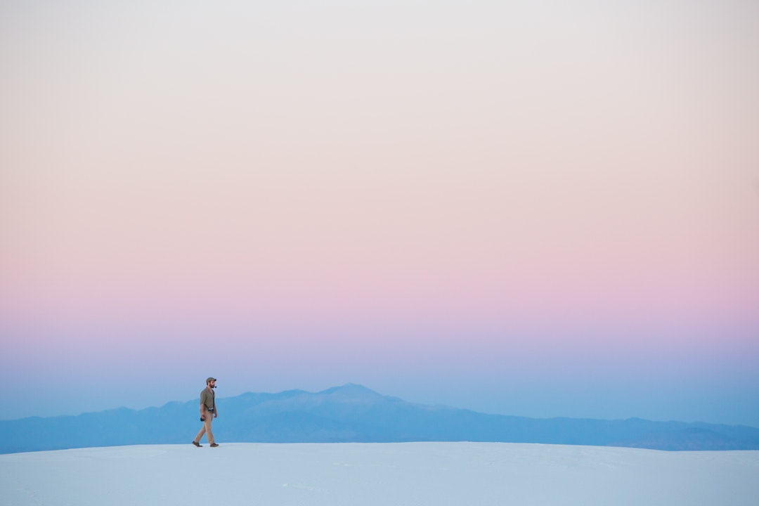 A dreamy shot of a man walking along a white sand dune with a mountain range on the horizon