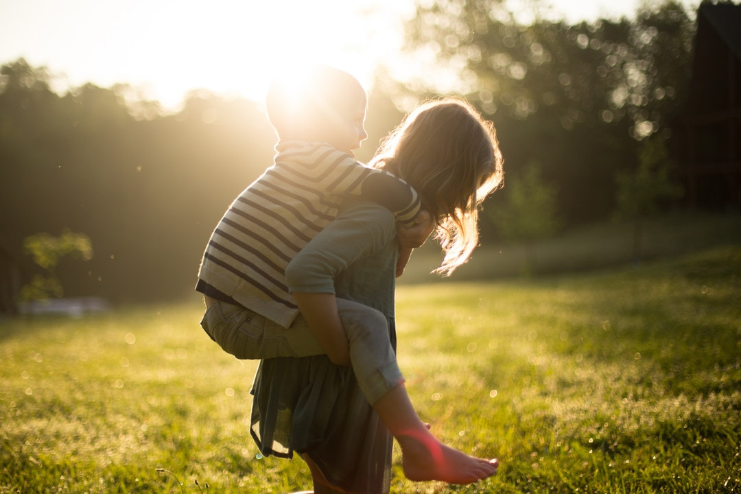 boy riding on girl's back outdoors during daytime