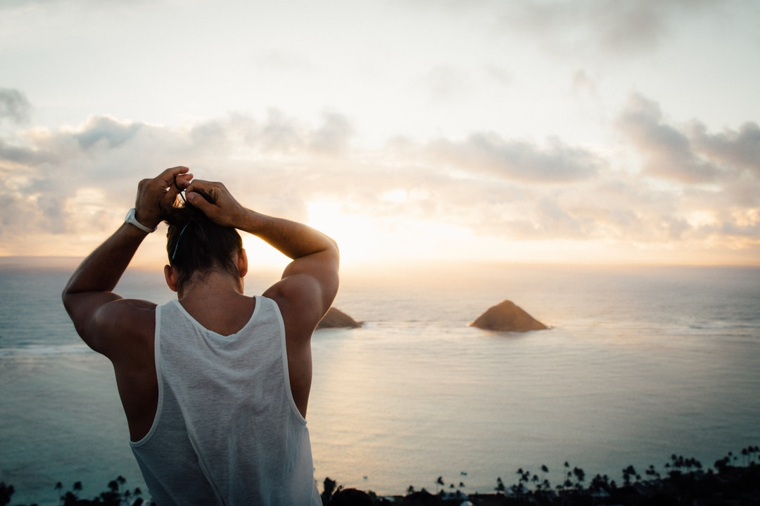 A man standing on a mountain by the coast putting his hair into a bun